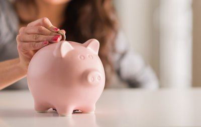photo of woman's hand inserting a coin into a piggy bank