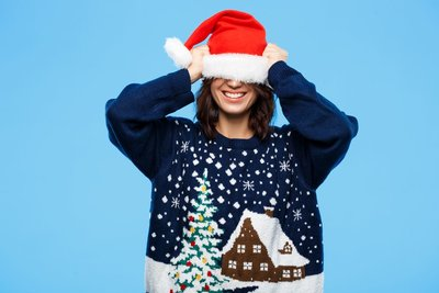 woman with a chrismas hat on her head wearing a blue cute christmas sweater