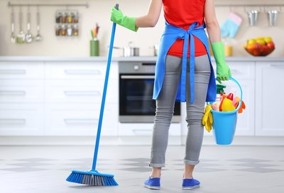 woman holding a broom and cleaning supplies, wearing an apron and gloves