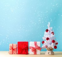 snowy background with a white christmas tree and red-wrapped gifts