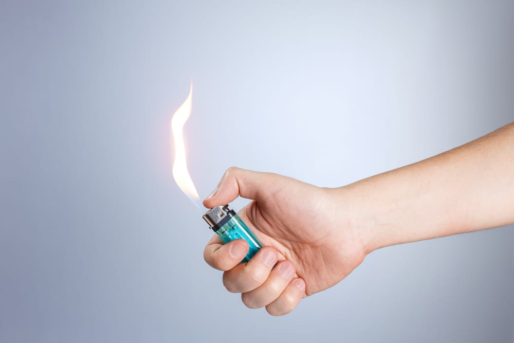 lighting a lighter with a large flame on a grey background