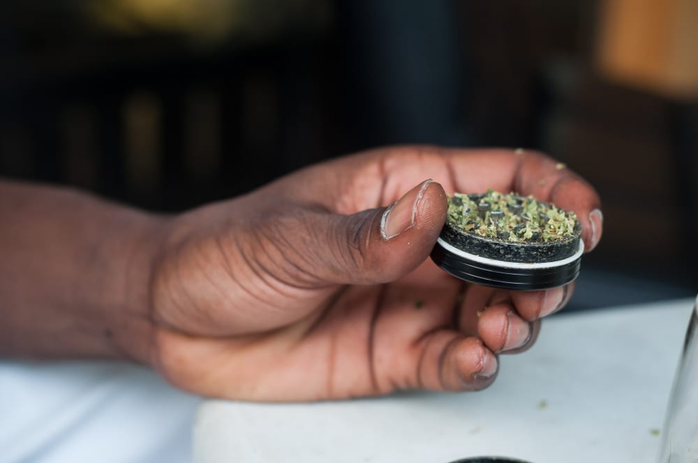man holding a grinder of weed